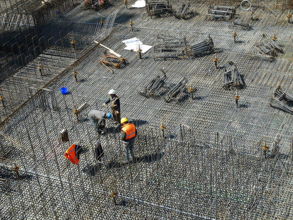 Rakennustyömaan osa ylhäältä päin. Miehiä raudoittamassa.
